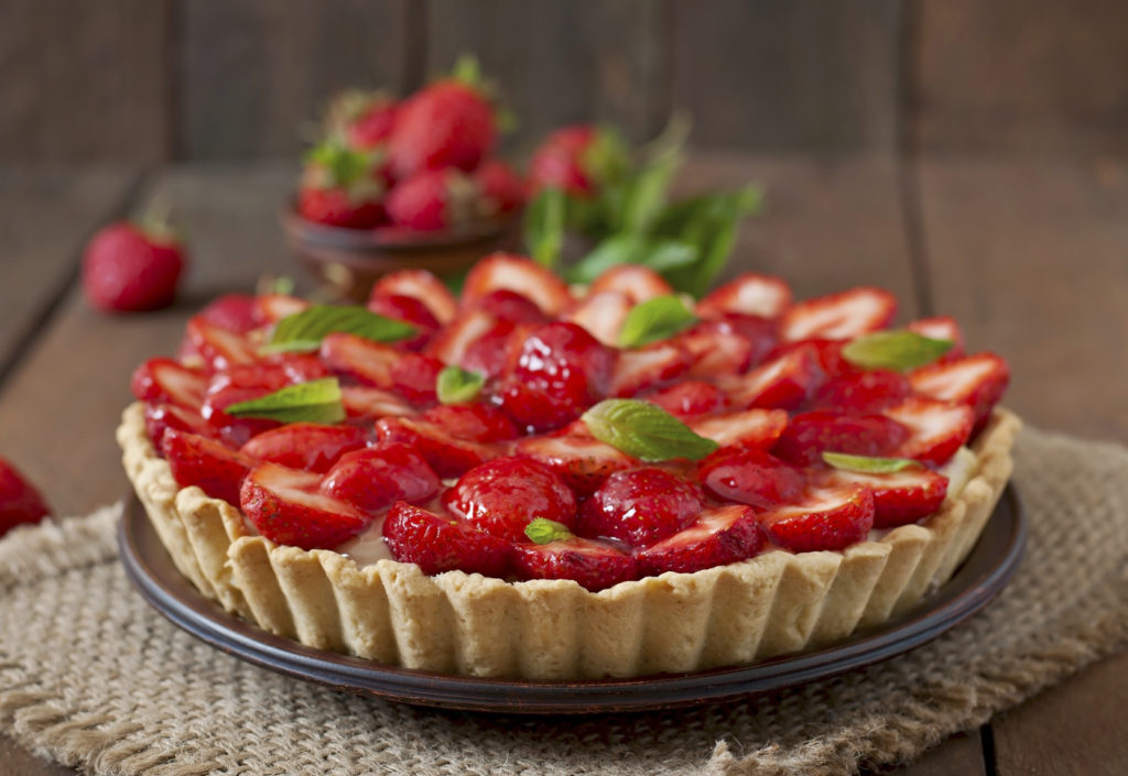 Tart with strawberries and whipped cream decorated with mint leaves